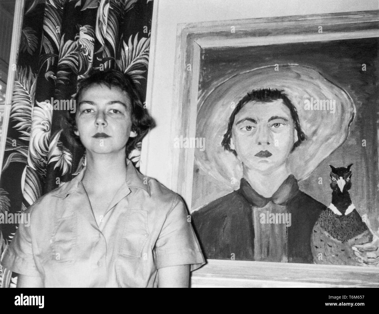 Flannery O'Connor (1925-1964), Southern Gothic novelist and short story writer, standing next to a 1953 self portrait where the author is holding a pheasant. - Stock Image