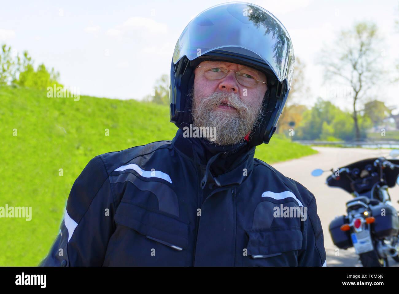 Mann mit langem Bart, Brille und Motorradhelm, steht am Ufer des Rhein - Stock Image