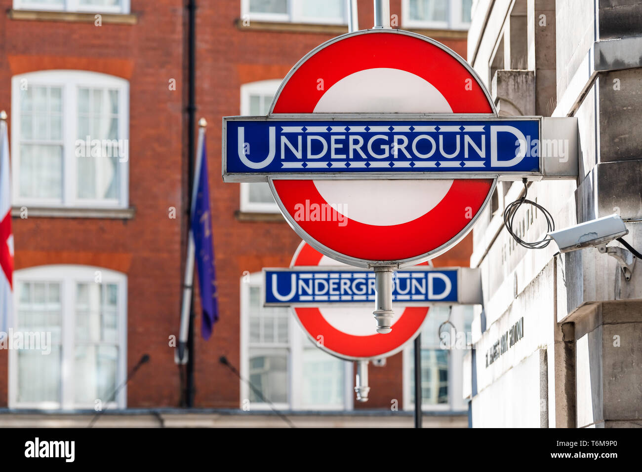 London, UK - June 22, 2018: Closeup of Underground tube metro blue and red signs on street road with flags and logo - Stock Image