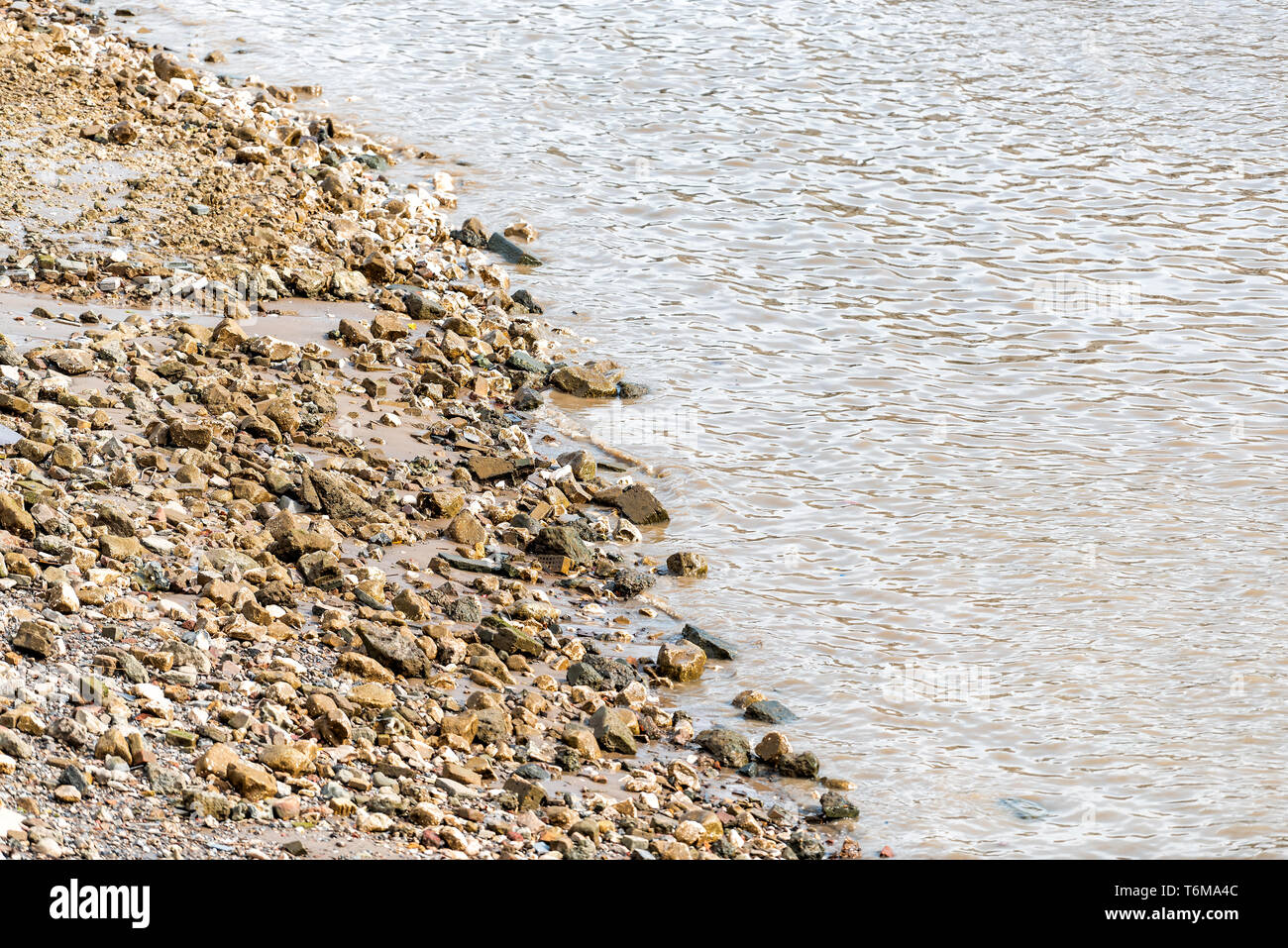 High angle closeup of Thames River in London with polluted dirty water and rocky beach shore on sunny day with brown color - Stock Image