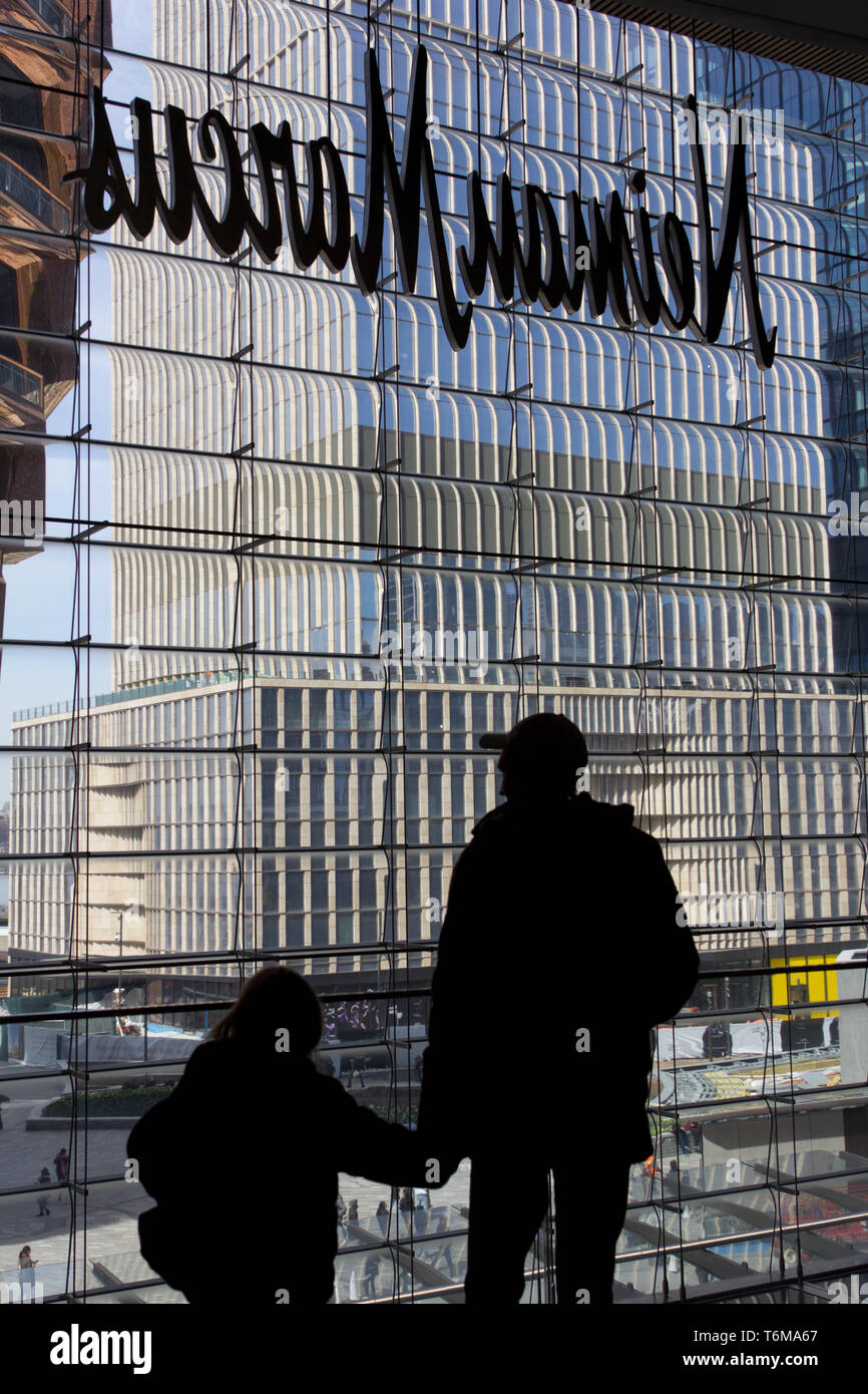 In a silhouetted back view, a man wearing a baseball cap holds the hand of a young girl as they look through a window of the Hudson Yards mall out onto the temporarily named Vessel steel sculpture partially visible on the left, with a high-rise building still under construction to the right, and people in the courtyard below. Above their heads is the reverse side of a Neiman Marcus department store sign. The Hudson Yards complex, which debuted 15 March 2019, to controversy about whether it was too elitist, encompasses retail, residential, restaurants, cultural institutions, and public space. - Stock Image