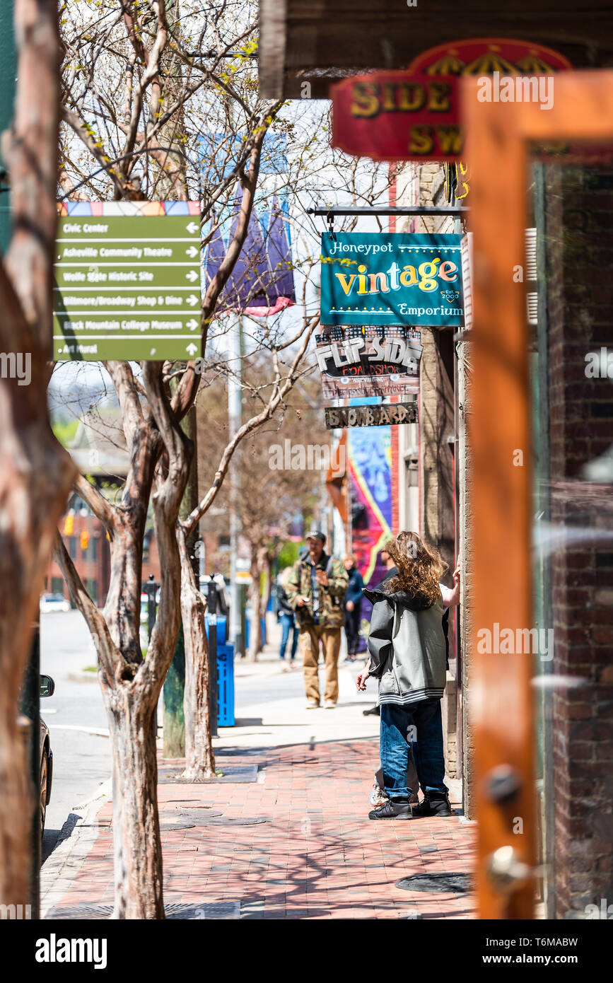 Asheville, USA - April 19, 2018: Downtown old town street in North Carolina NC city with sign for vintage emporium stores, shops - Stock Image