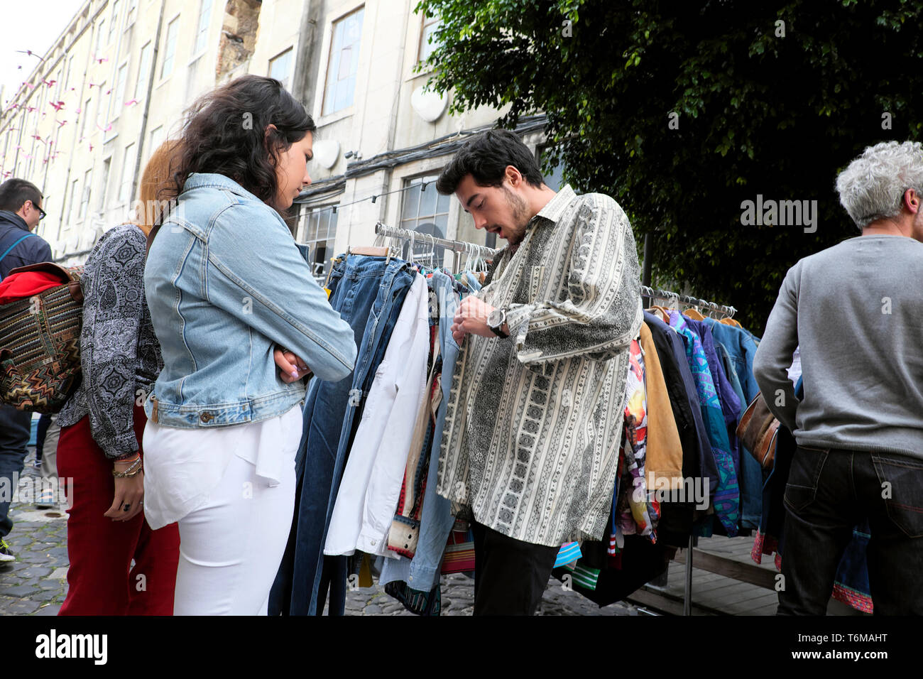 A Portuguese man trying on a vintage shirt on a second hand recycled clothing stall at the LX Factory Market in Lisbon Lisboa Portugal  KATHY DEWITT - Stock Image