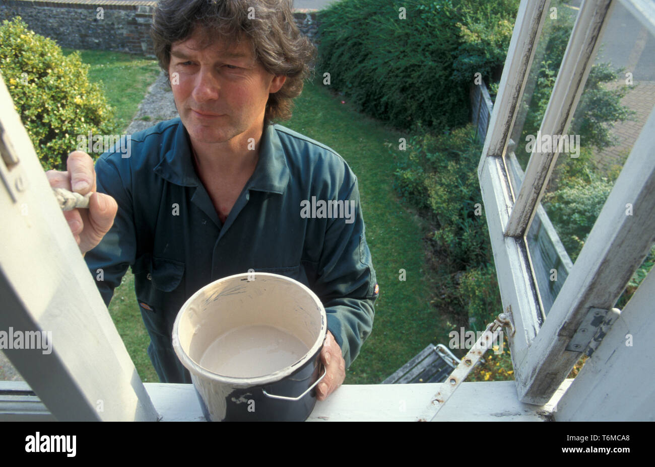 middle aged man painting cottage window frames Stock Photo