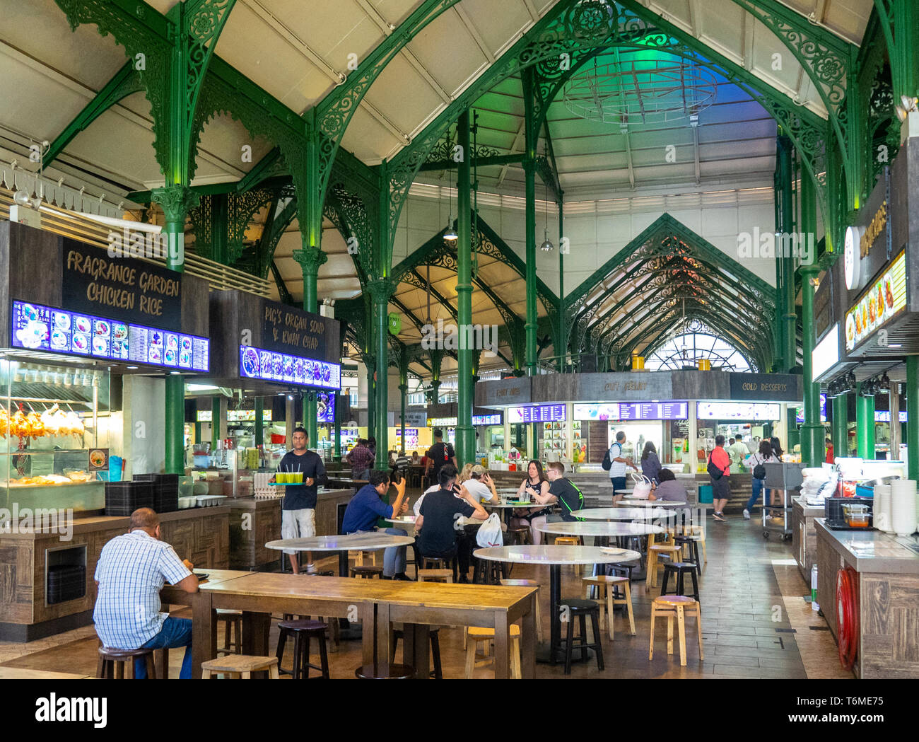 green painted cast iron latticework, and diners seated at tables Lau Pa Sat Hawker Food markets in downtown Singapore. - Stock Image