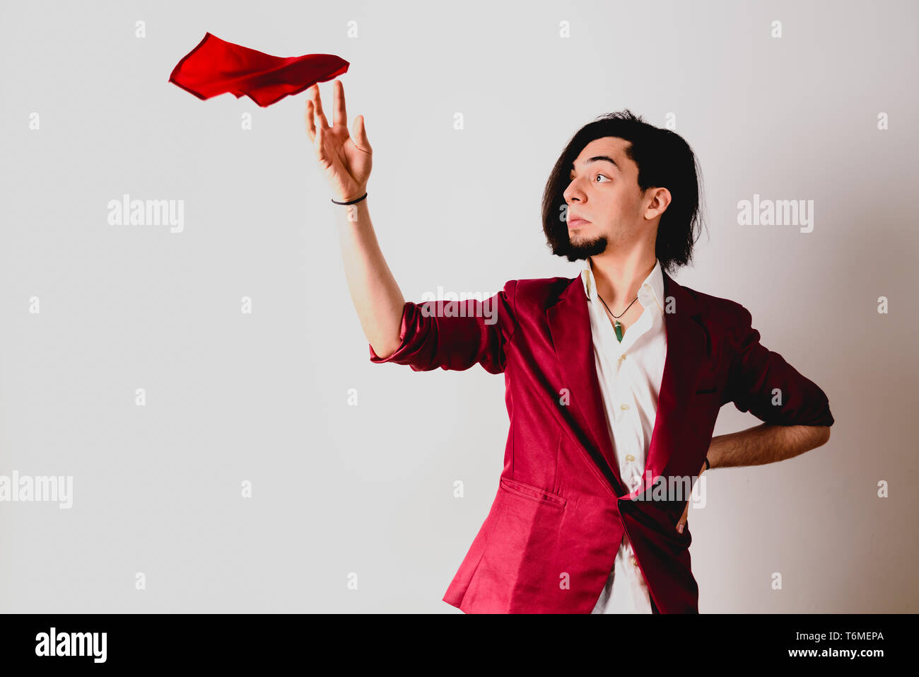Portrait of young magician handling ropes and bandanas to do magic tricks, isolated on white. - Stock Image