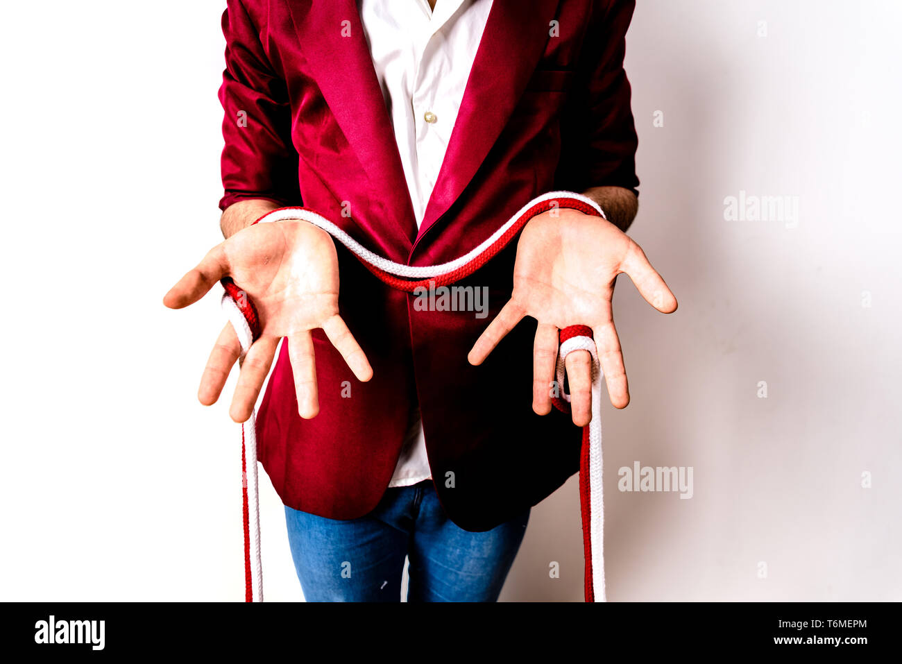 Magician hands handling ropes and bandanas to do magic tricks, isolated on white. - Stock Image