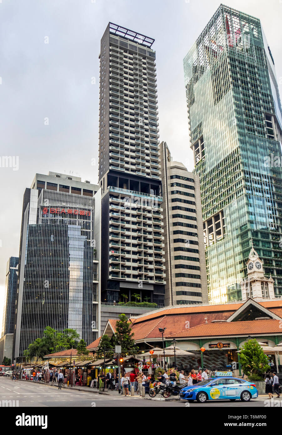 Office and residential towers skyscrapers towering over Lau Pa Sat hawker food markets in downtown Singapore. - Stock Image