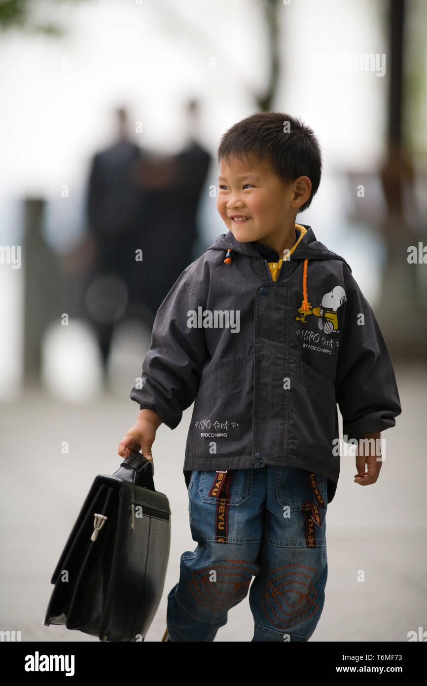 Smiling young boy carrying a suitcase. - Stock Image