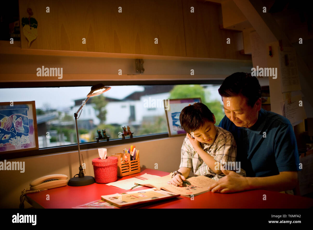 Mature man sitting reading with his son. - Stock Image