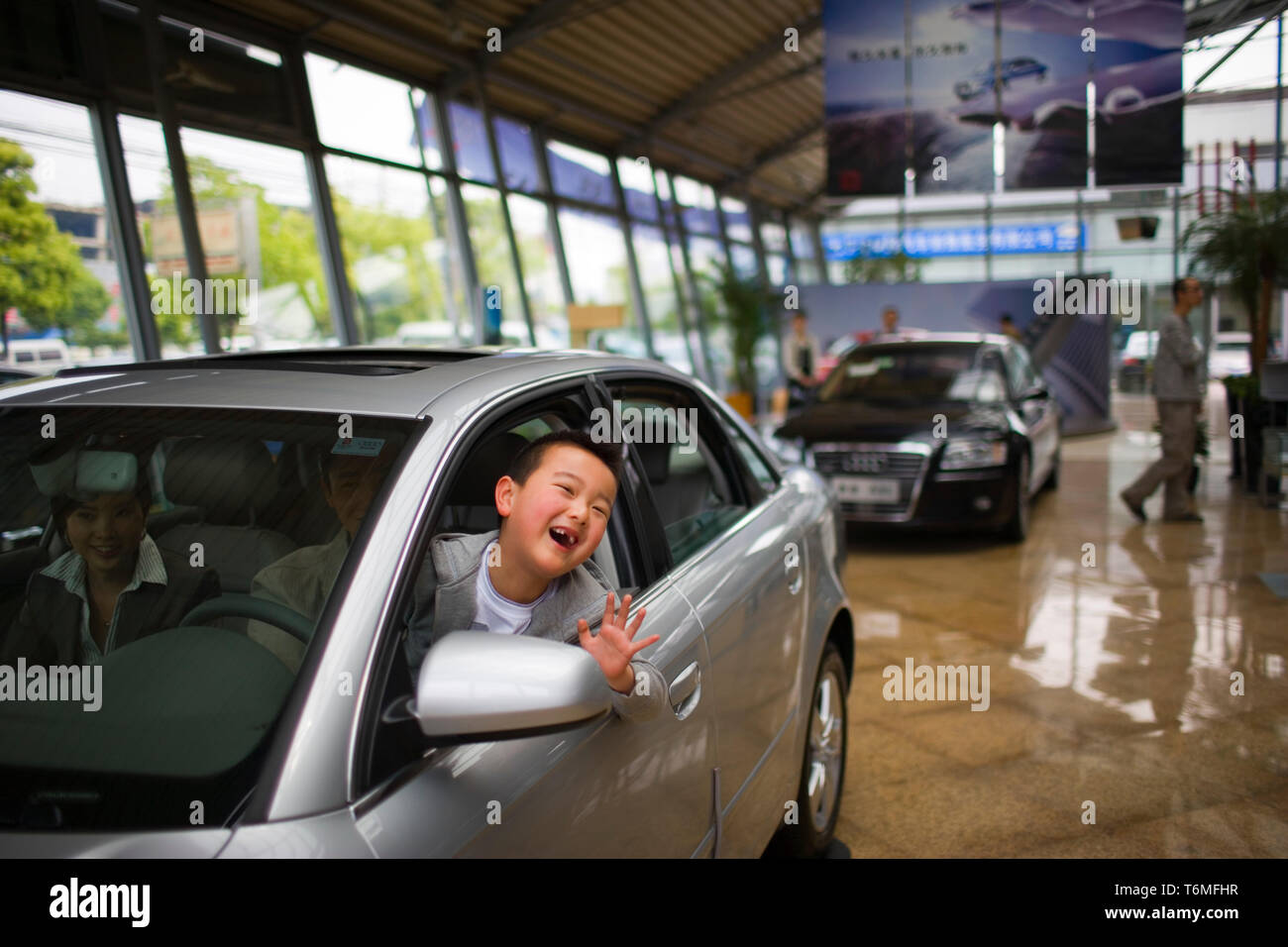 Portrait of a young boy waving out the window of a car he is sitting in with his parents inside a showroom. - Stock Image