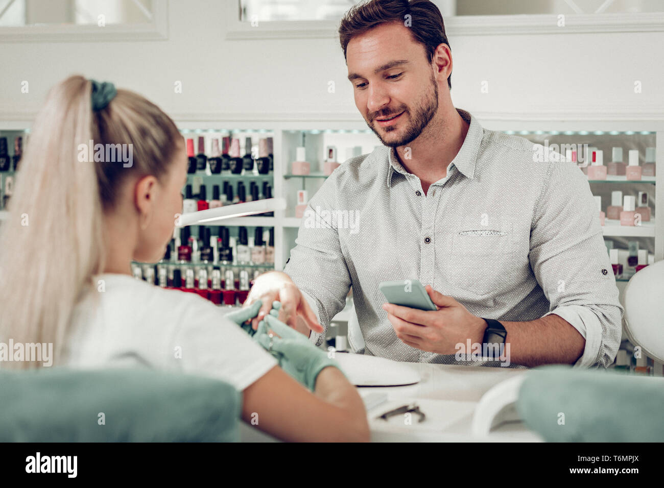 Handsome bearded dark-haired man treating his nails in special salon - Stock Image