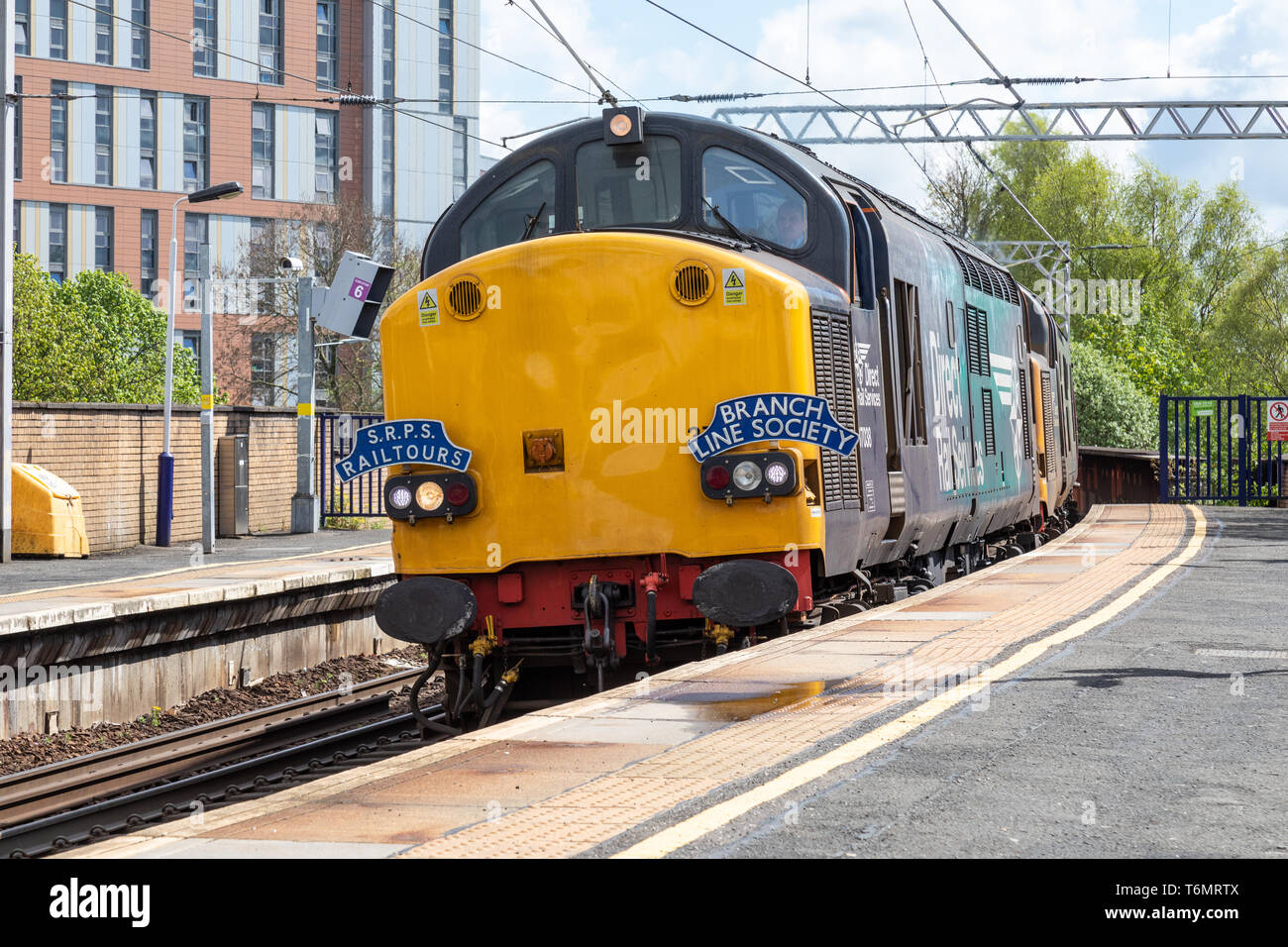 37038 powers through Partick station on the suburban Glasgow train network whilst pulling the SRPS Branch Line Society rail tour - Stock Image
