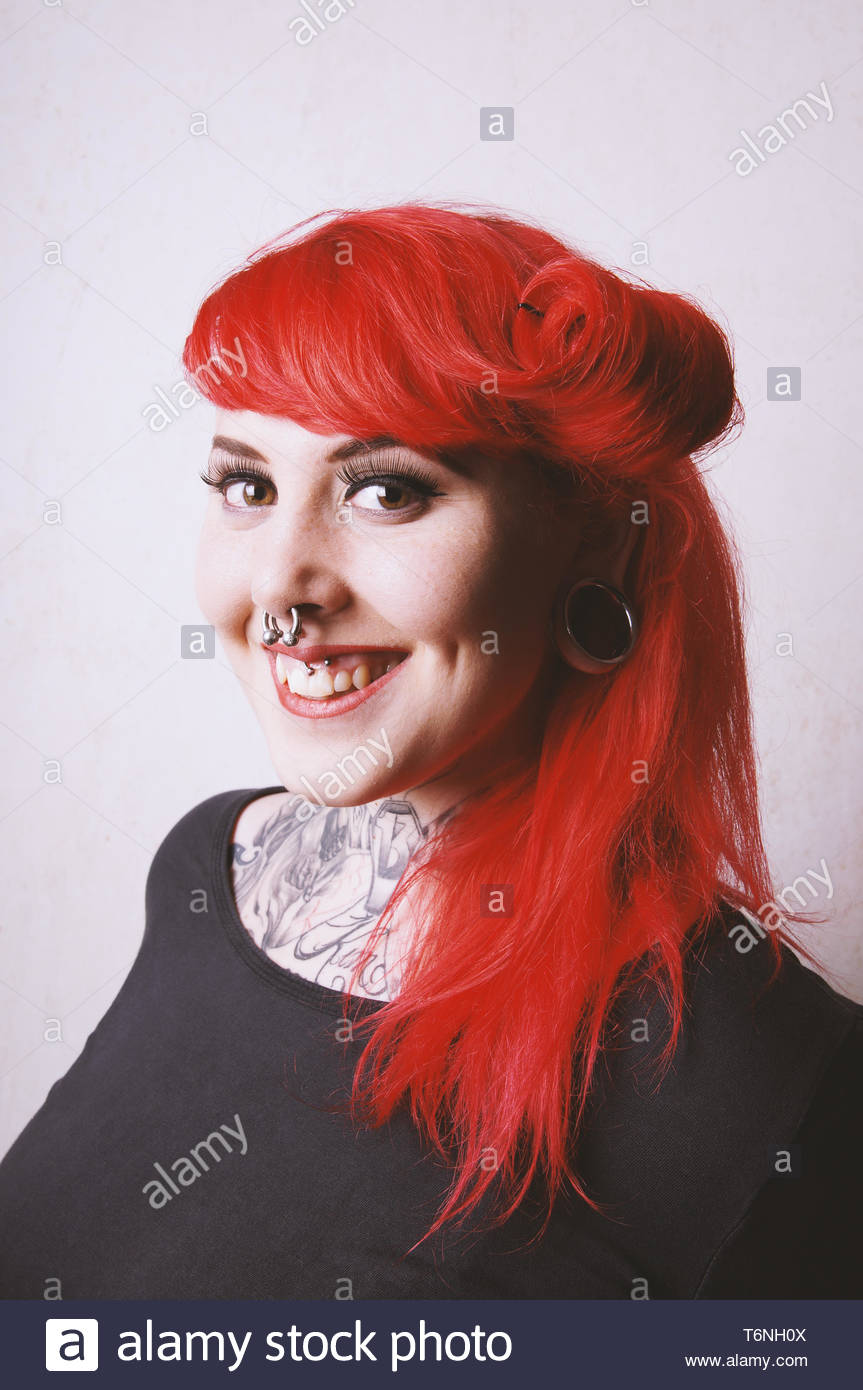 pierced and tattooed young woman with toothy smile Stock Photo