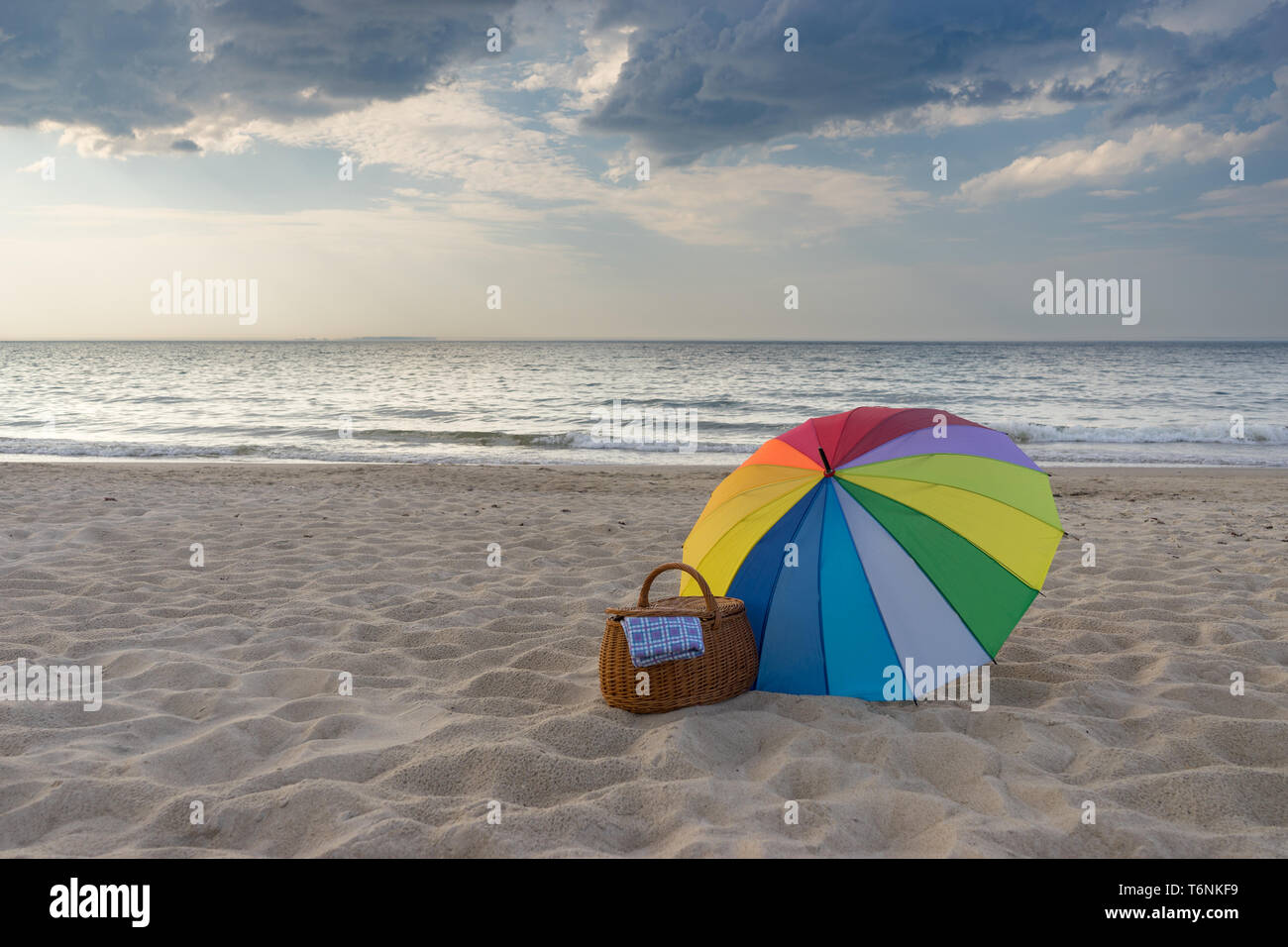 Multicolored umbrella and picnic basket against scenic beach and sea, weekend break concept - Stock Image