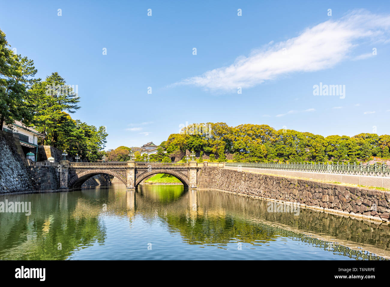 Tokyo, Japan reflection in pool moat by Imperial palace during spring day with royal castle and bridge - Stock Image