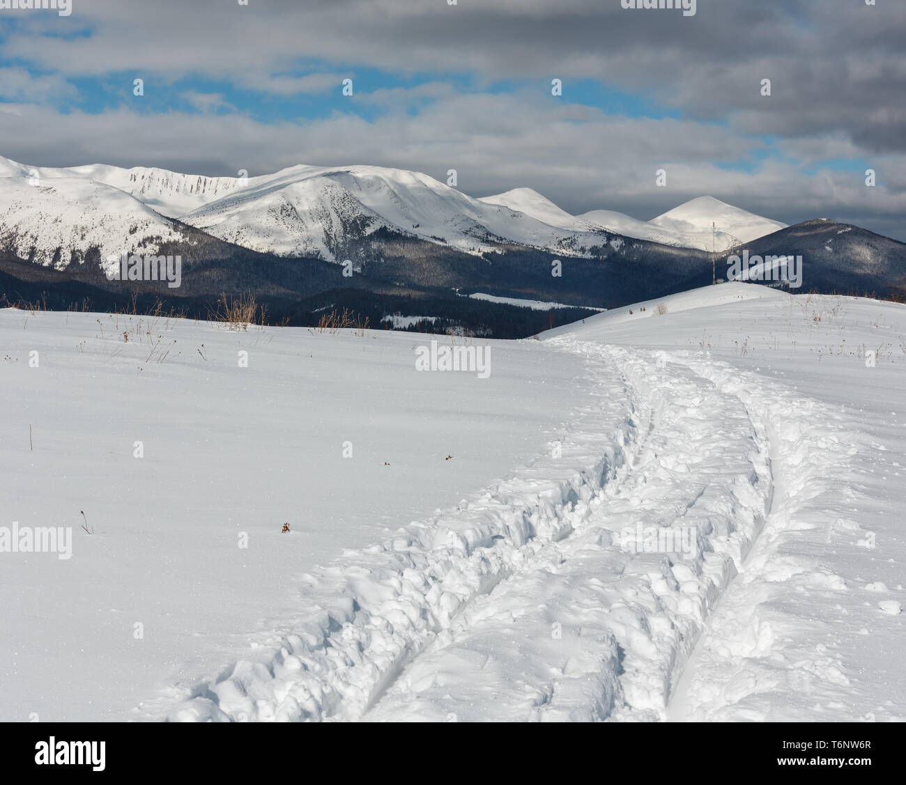 Sledge trace and footprints on winter mountain hill top Stock Photo