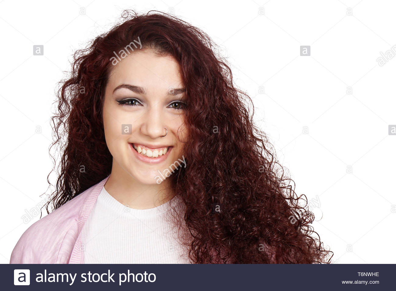 happy teenage girl with long curly hair and toothy smile - Stock Image