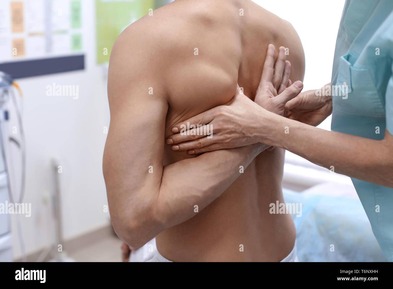 Orthopedist examining patient in hospital - Stock Image