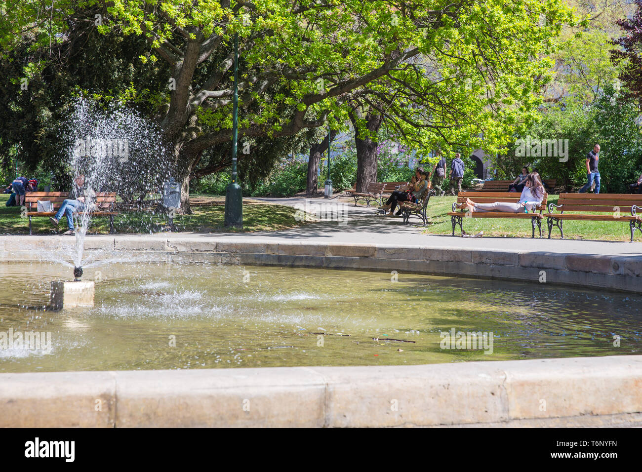 City Prague, Czech Republic. Fountain and tourists, girl talking on the phone, people sitting on the bench.. 2019. 25. April. Travel photo. - Stock Image