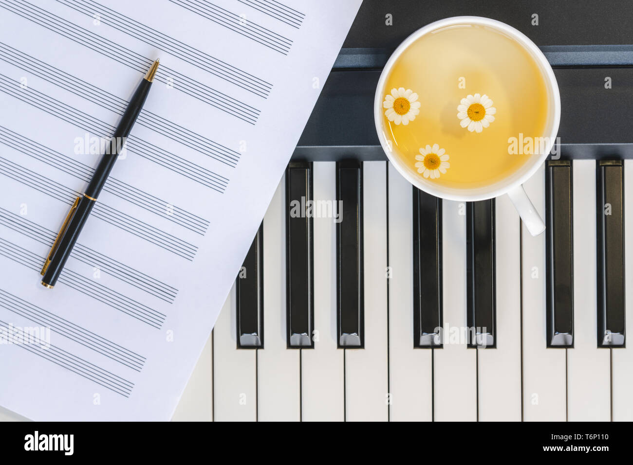 Cup of Chamomile Tea on a Piano Keyboard, Music Sheet and Pen. Still Life, Romance, Concept - Stock Image