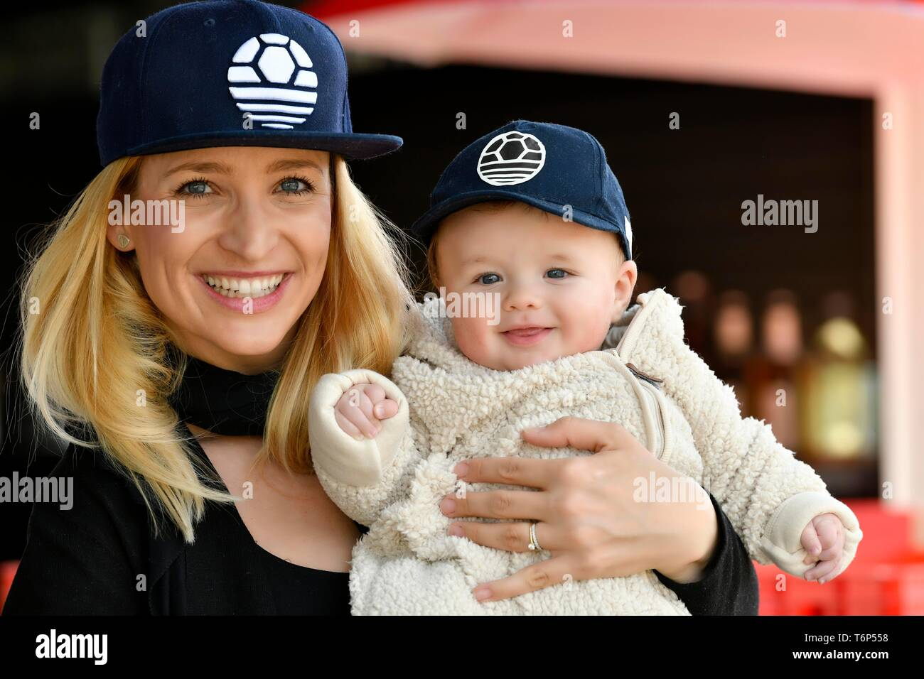 Mother and baby, 5 months, with the same caps, laugh, Baden-Wurttemberg, Germany - Stock Image