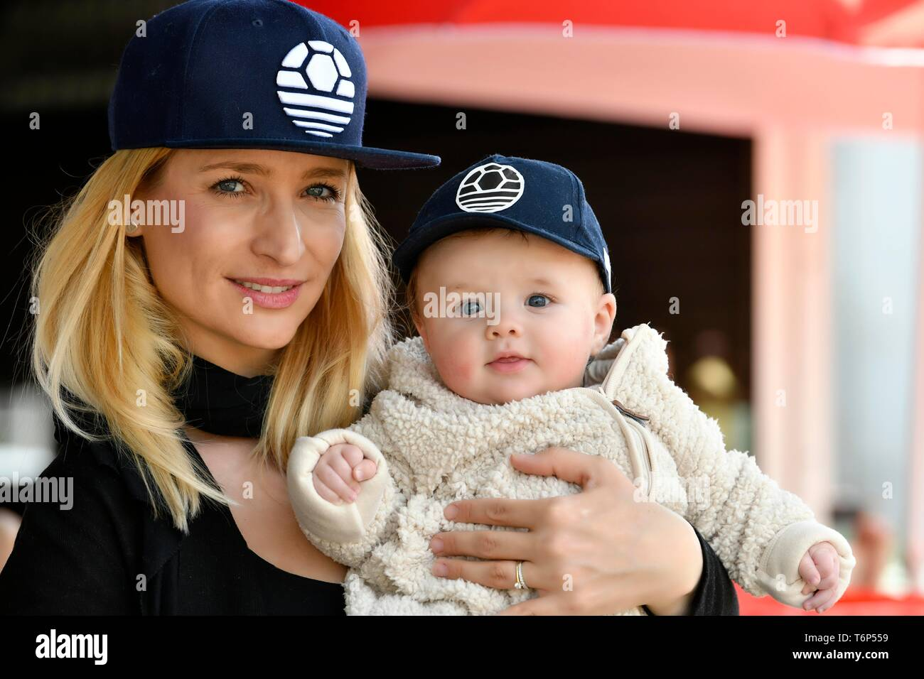 Mother and baby, 5 months, with the same caps, Baden-Wurttemberg, Germany - Stock Image
