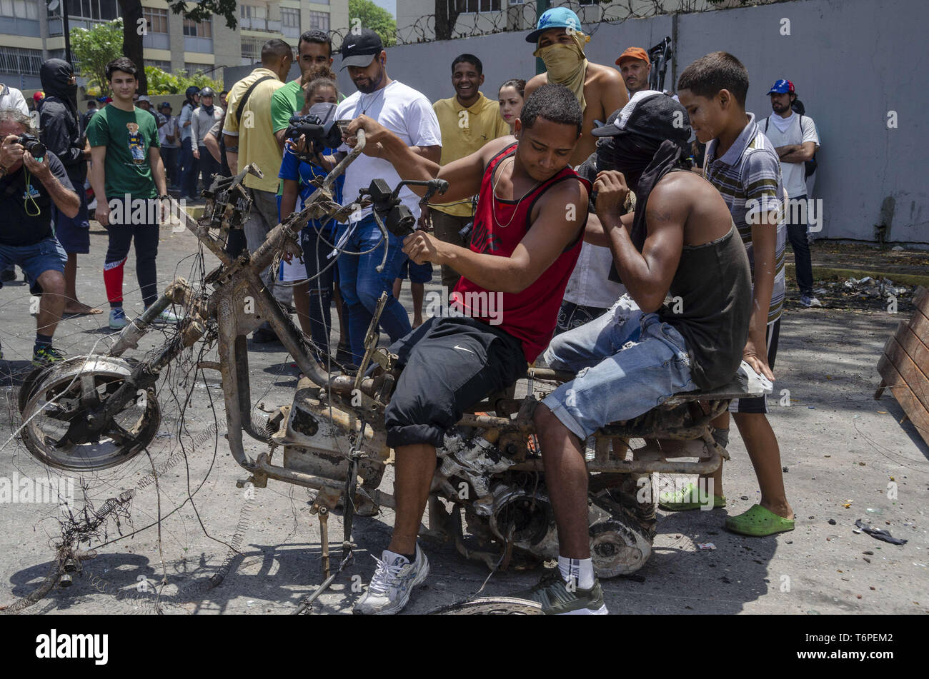 Caracas, Miranda, Venezuela. 1st May, 2019. Young people living on the streets (homeless) play with a burnt motorbike, remnants of the incidents that occurred on April 30.Thousands of Venezuelans went out to march and protest against Maduro's government on Labor Day in Caracas and others cities in Venezuela (Credit Image: © Jimmy VillaltaZUMA Wire) - Stock Image