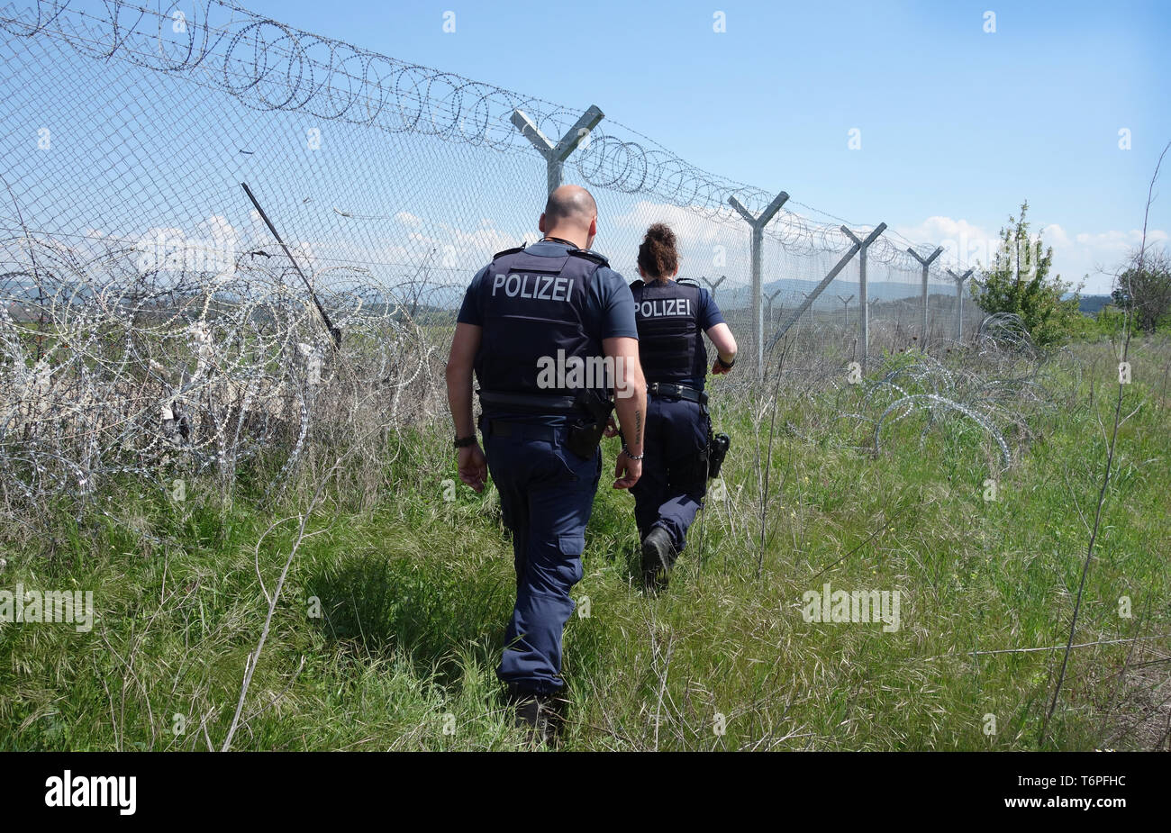 02 May 2019, Greece, Thessaloniki: The North Rhine-Westphalian police officers Muna Mougawaz and Alexander Rankovic are working for the EU border protection organisation Frontex at the border fence between Greece and North Macedonia. North Rhine-Westphalia's Interior Minister Reul visited North Rhine-Westphalian police officers who, as part of the EU border protection agency Frontex, are helping to secure the Greek border with northern Macedonia. The main aim of the officials is to prevent refugees and migrants from illegally arriving in Central Europe from Northern Macedonia. Photo: Alexia An - Stock Image