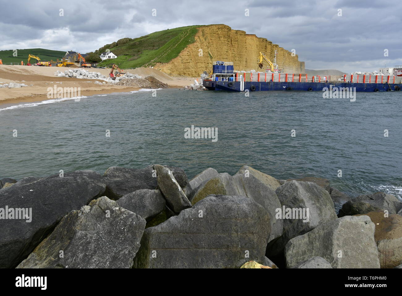 West Bay, Dorset, UK. 2nd May 2019. A large coastal defence is underway at West Bay in Dorset. Large blocks are delivered by boats and off loaded into the sea front by bucket loads. The stones come from Scotland where its picked up by large mechanical clasps and driven up the pebble beach. The sea front is where the TV show Broadchurch was filmed.Picture Credit: Robert Timoney/Alamy Live Newss - Stock Image