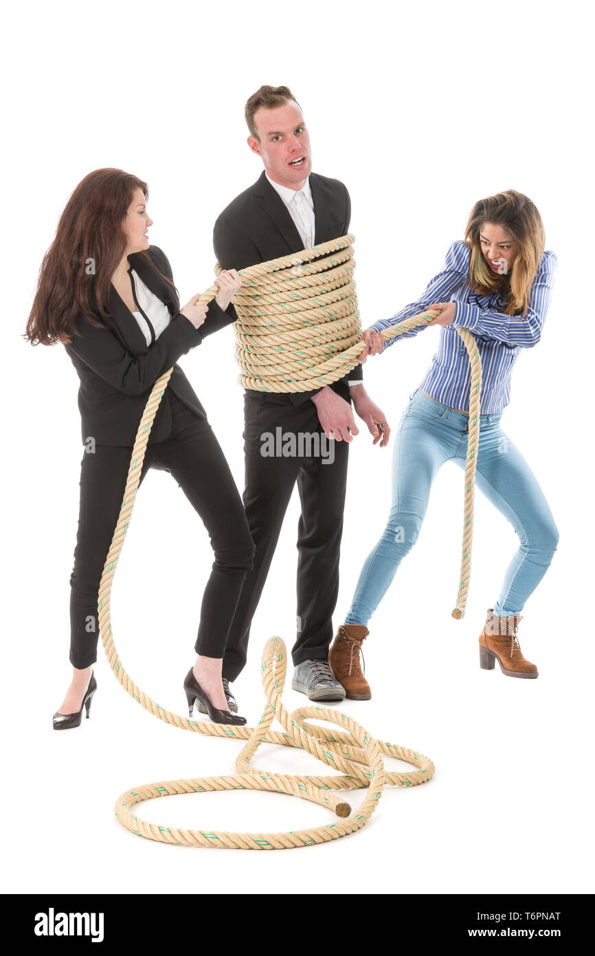 Two angry woman tying a business man with rope - Stock Image