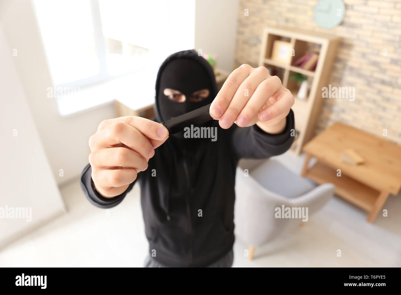 Thief putting sticky tape onto camera of alarm system, indoors - Stock Image
