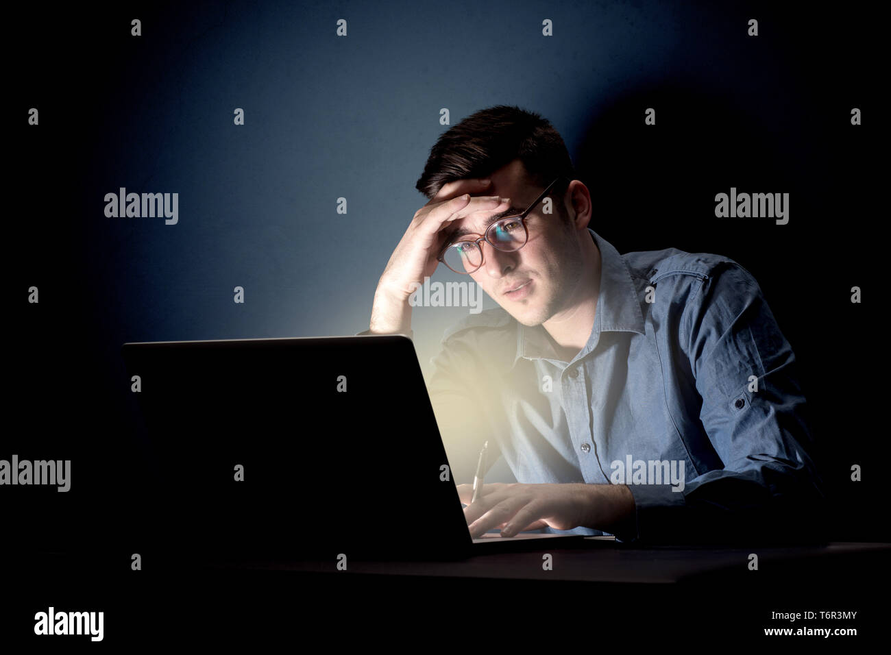 Young handsome businessman working late at night in the office with a dark background - Stock Image