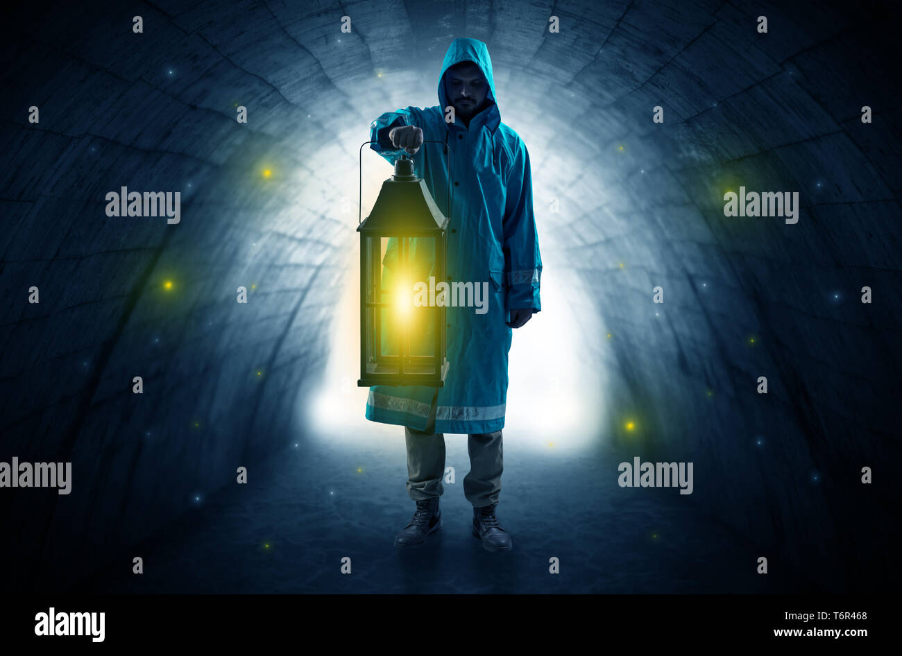 Ugly man in raincoat walking with glowing lantern in a dark tunnel - Stock Image