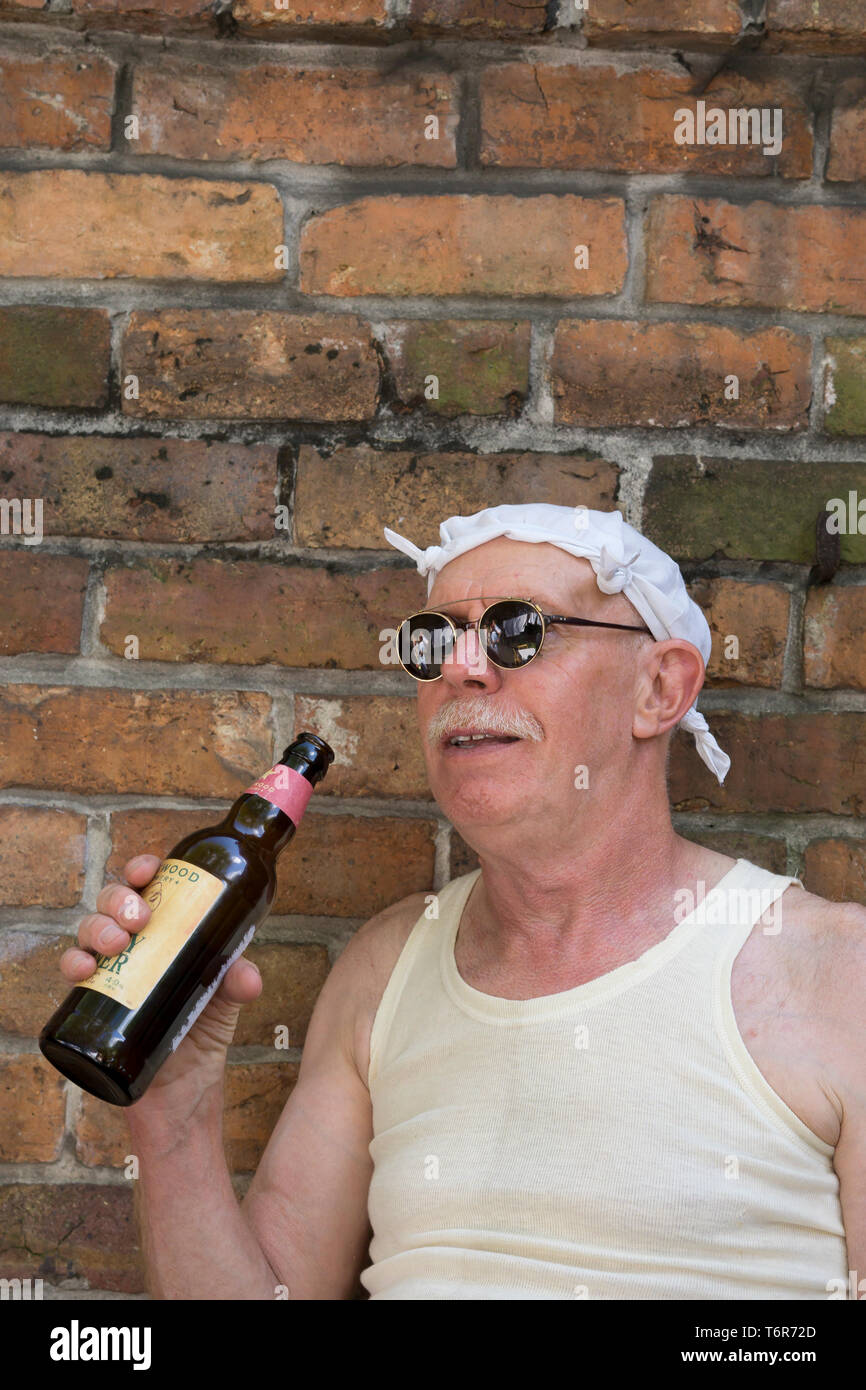 Close up of senior British man in white vest wearing dark sunglasses & white knotted handkerchief on head. Chap drinking bottle of beer by brick wall. - Stock Image