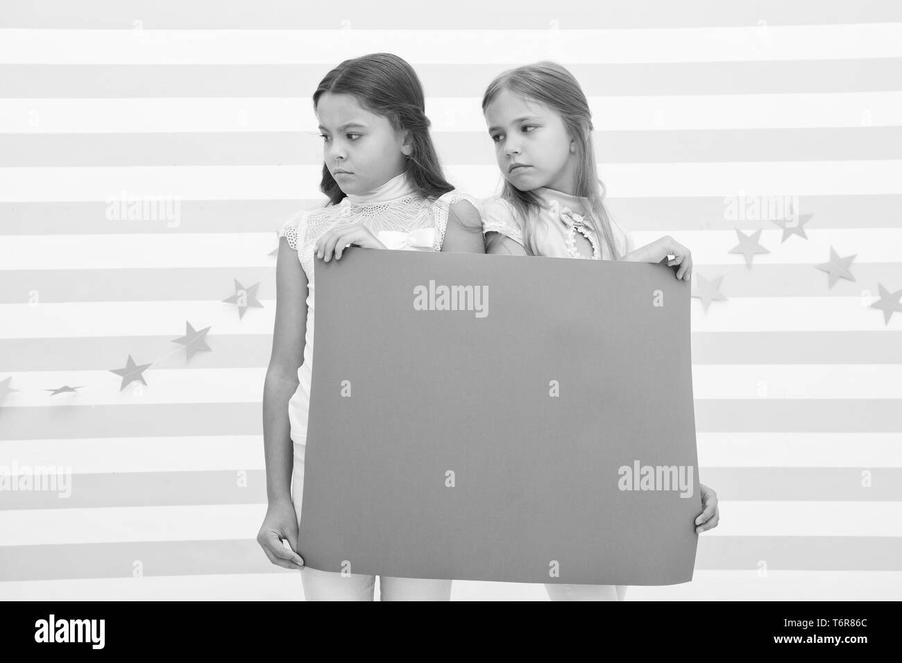 Regret to inform you. Girls hold advertisement poster copy space. Children hold advertising banner. Sad kids with blank paper advertisement. Advertisement concept. Your advertisement in good hands. - Stock Image