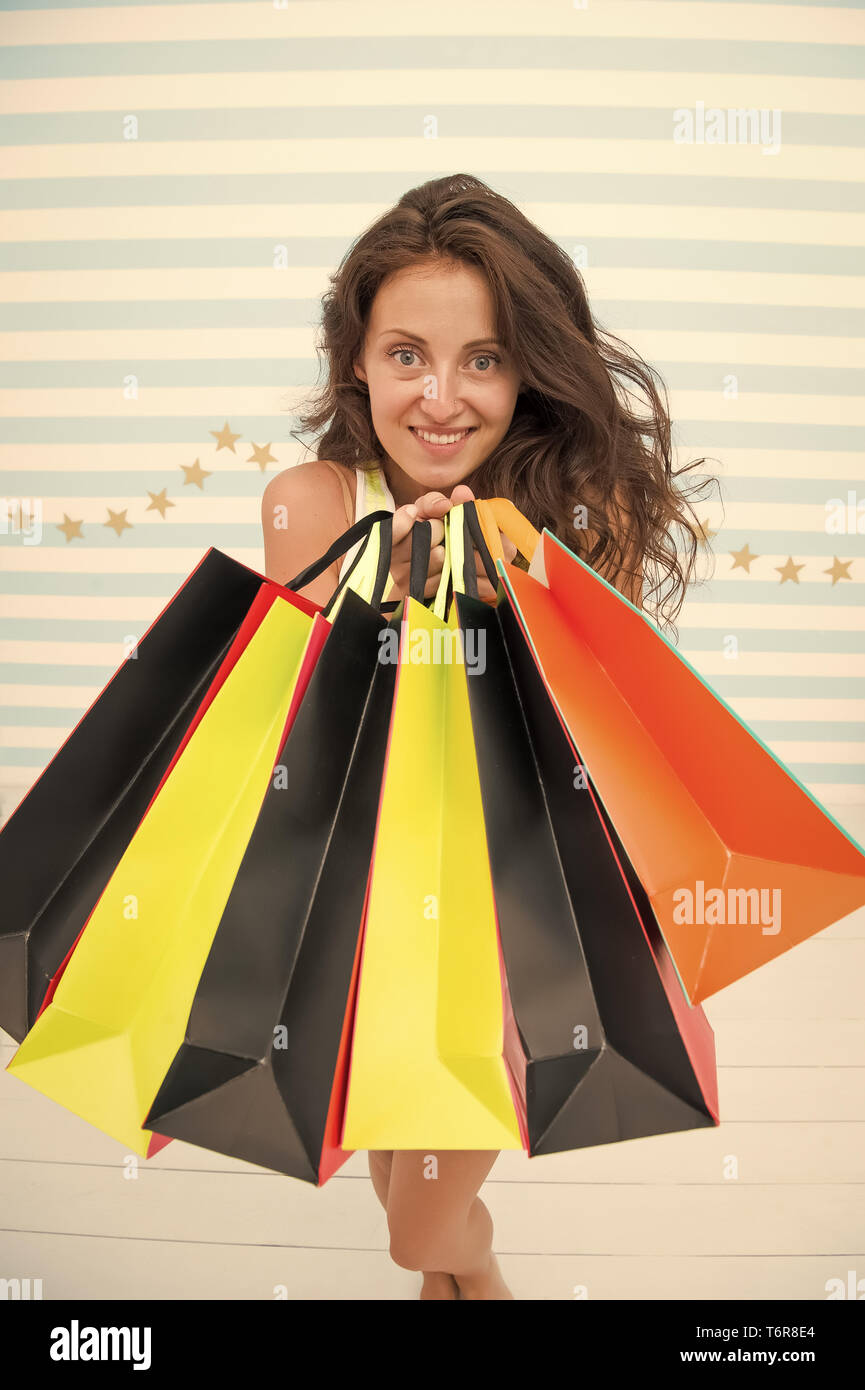 Woman carries bunch shopping bags striped background. Finally bought favorite brand. Tips shop sales. Girl satisfied with shopping. Profitable purchase black friday. Feel free buy everything you want. - Stock Image