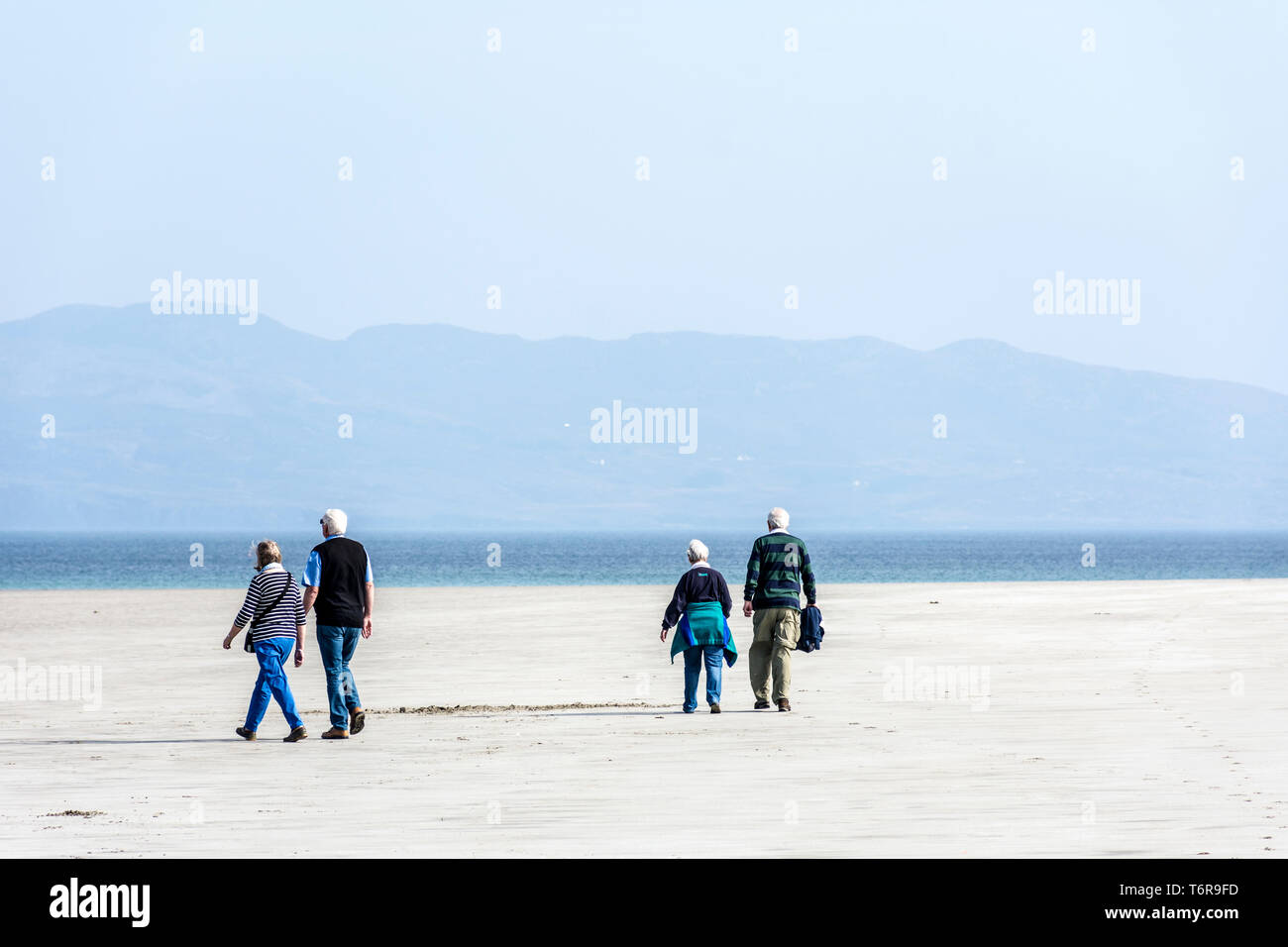 Two senior couples on a beach walking, County Donegal, Ireland - Stock Image