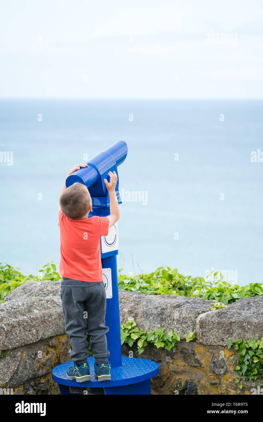 Little boy looking through the telescope - Stock Image