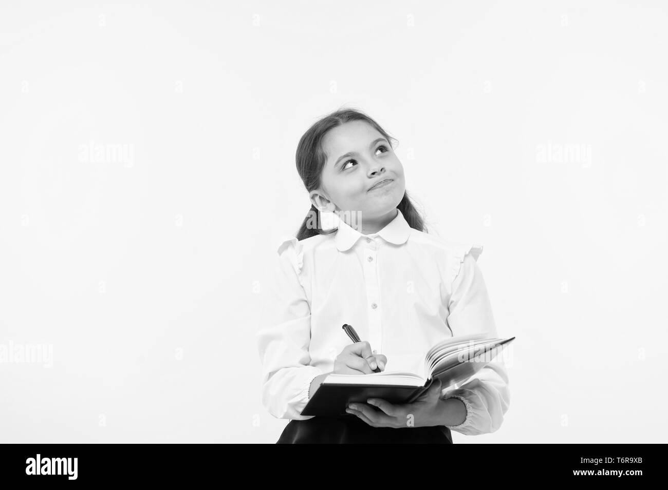 Child school uniform kid doing homework. Child girl school uniform clothes hold book and pen. Girl cute write down idea notes. Notes to remember. Write essay or notes. Personal schedule. Making notes. - Stock Image