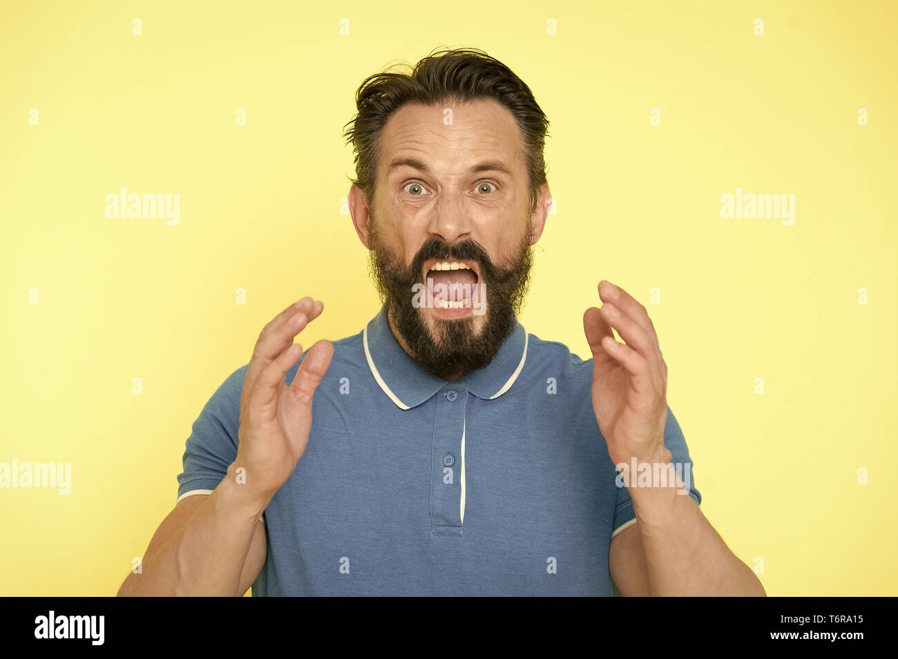 Overwhelmed with emotions. Handsome shouting mature man screaming standing against yellow background. Man bearded irritated annoyed can not keep calm anymore. Stop annoying him. Stressful adult life. - Stock Image