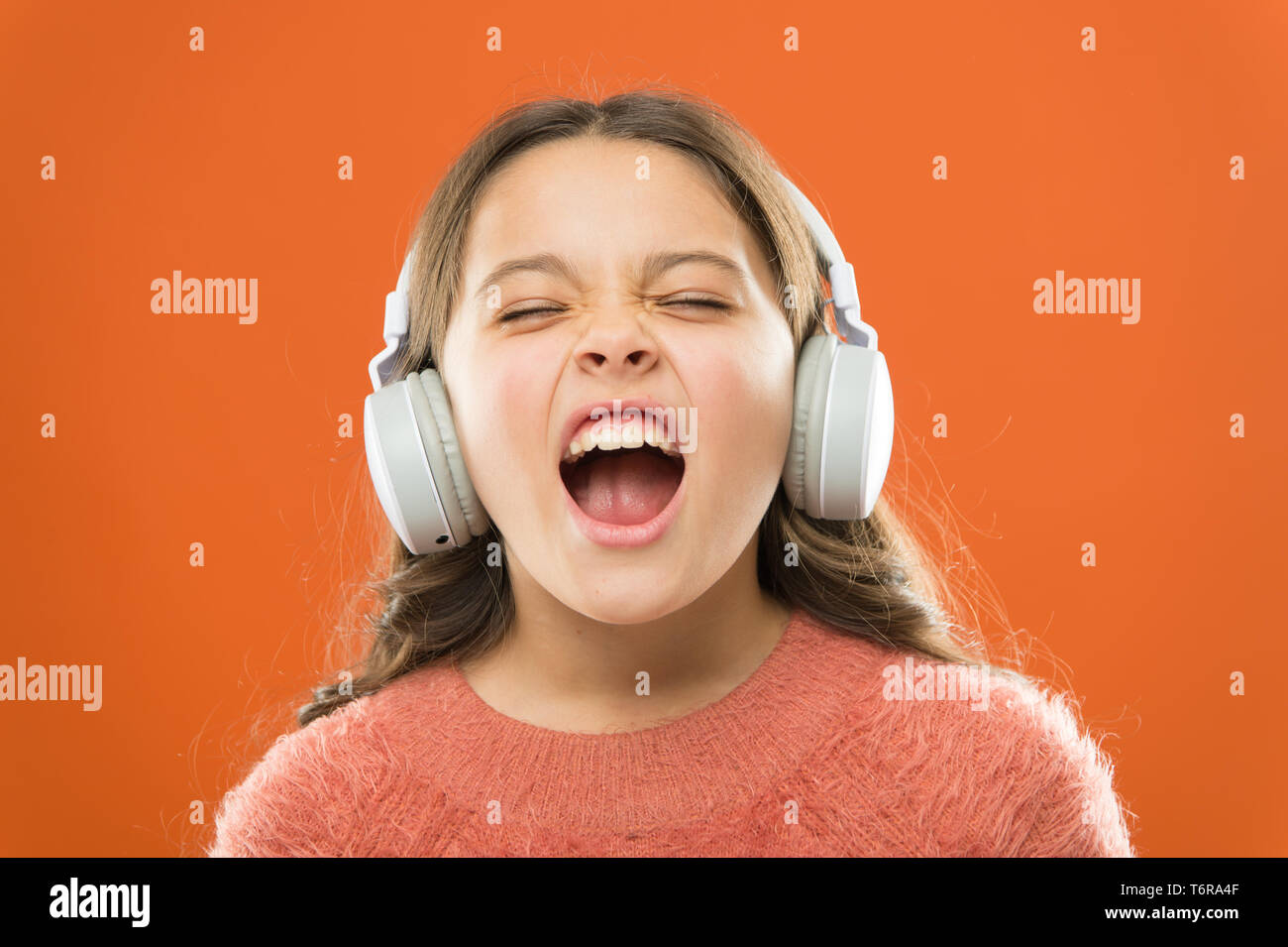 For better vocal performances. Adorable small child doing vocal on song. Little girl listening to music and singing vocal melody. Talented singer or vocalist training her vocal in wireless headphones. Stock Photo