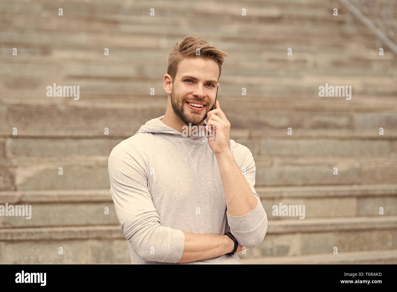 Keep in touch. Man bearded walks with smartphone, urban background with stairs. Man pleasant smiling face speaks on smartphone. Guy pleased answer call on smartphone. Pleasant conversation. - Stock Image