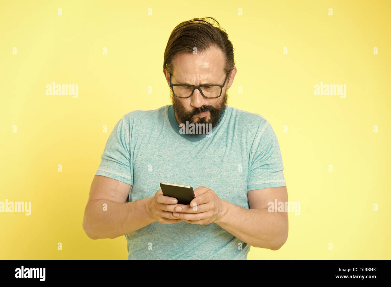 Guy eyeglasses puzzled face use smartphone. Man user interact application smartphone. Guy bearded mature interact mobile interface application. Hard to get used to digital gadget for mature people. - Stock Image