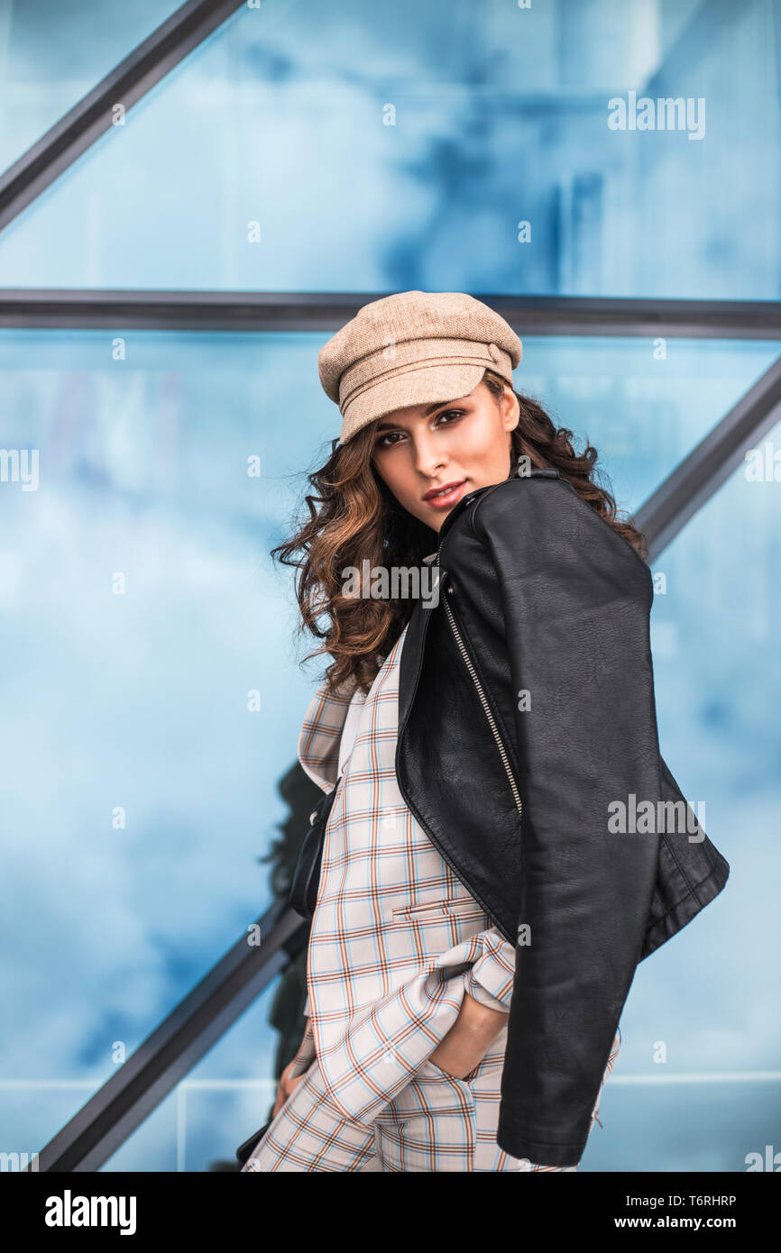 Fashionable young woman posing against glass windows outdoors. Stock Photo