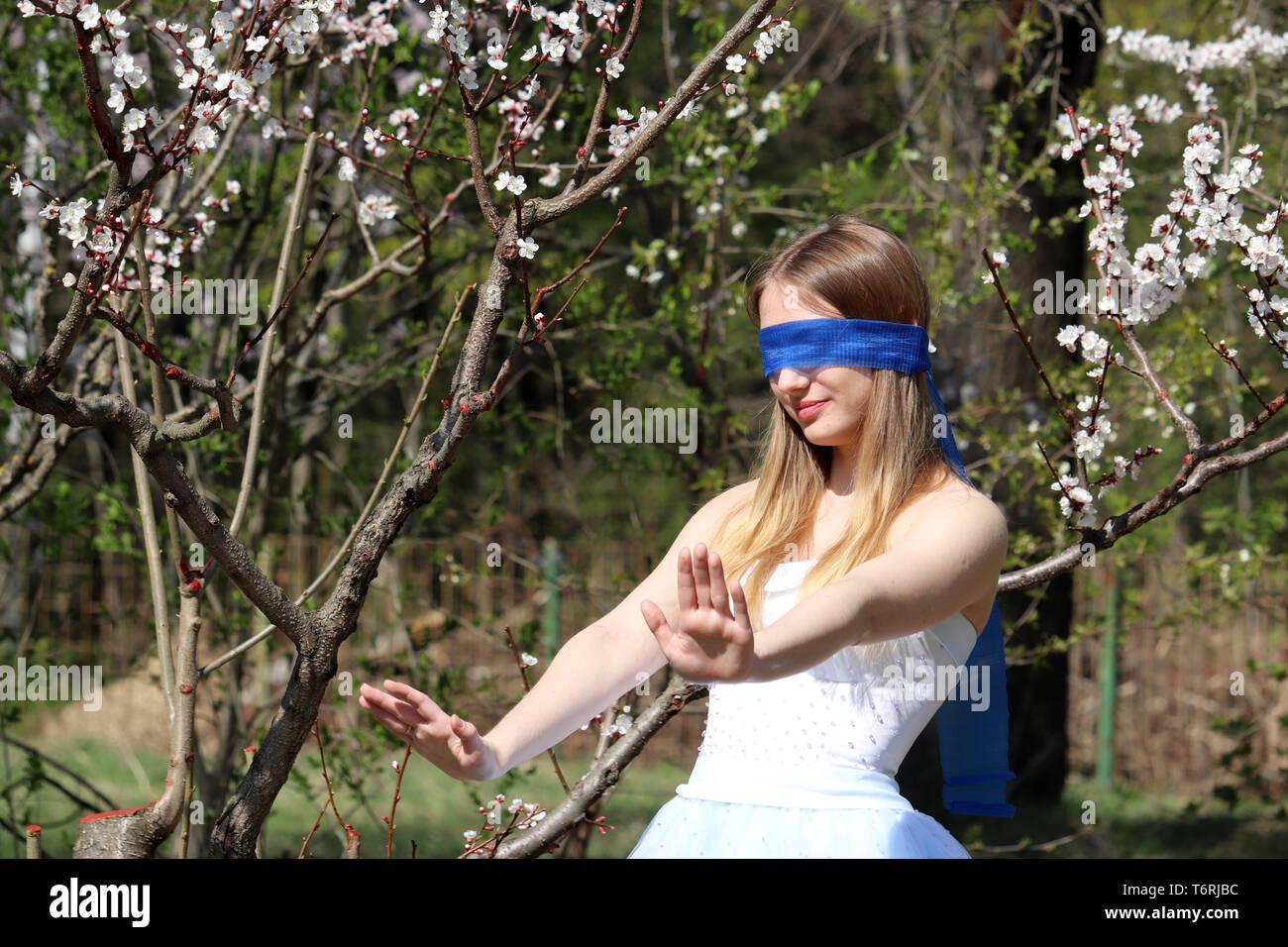 Cherry blossom season in Moscow Botanical garden. Blindfolded girl posing on sakura tree background, leisure in spring - Stock Image
