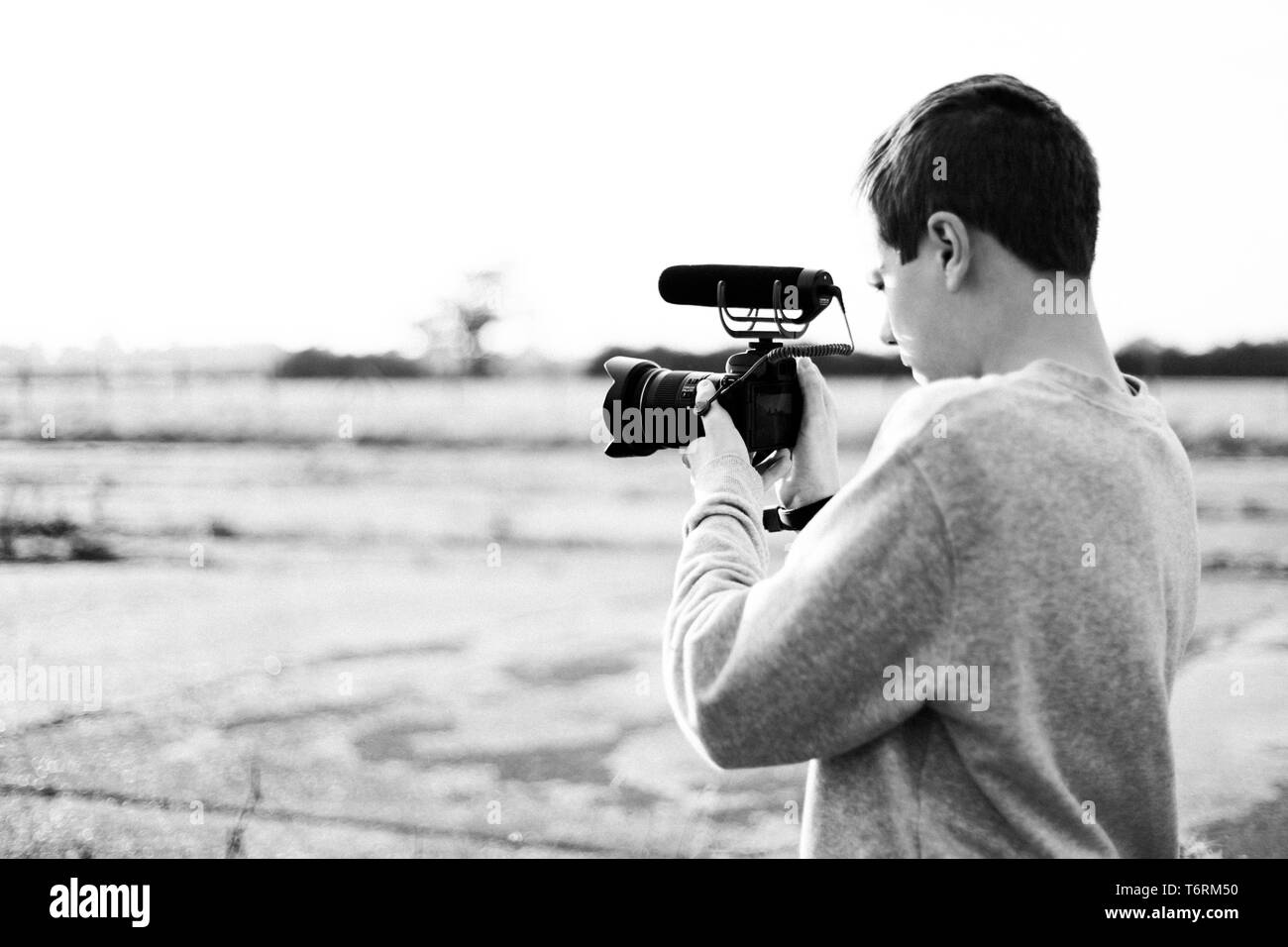 Young male videographer studying and using mirrorless camera with microphone attachment to create a video.  Sunset with glow highlights the contrast. - Stock Image