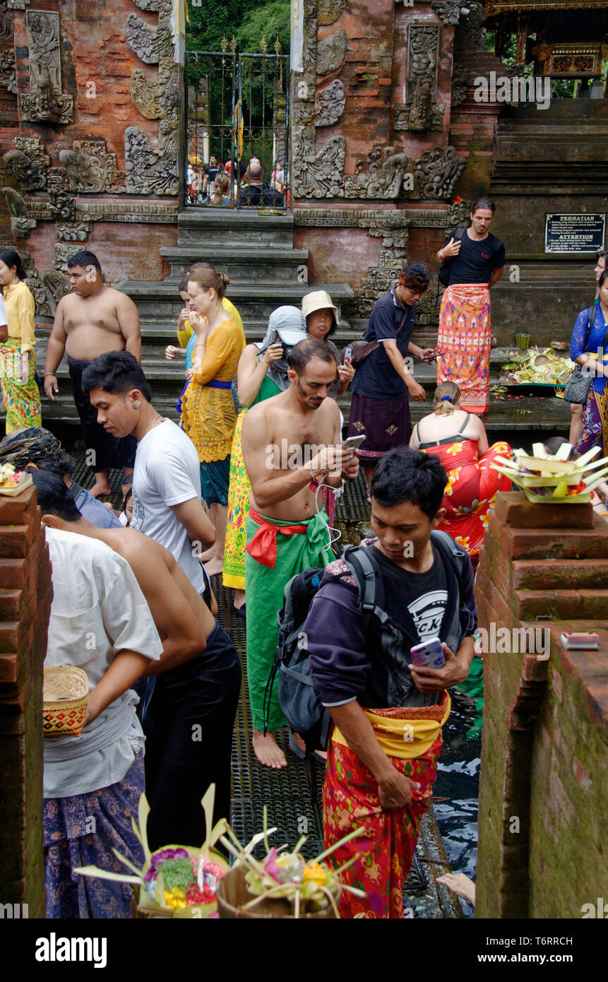 Tourist taking photo on cell phone of worshippers cleansing at Tampak Siring, the Holy Spring Water Temple near Ubud in Bali, Indonesia - Stock Image