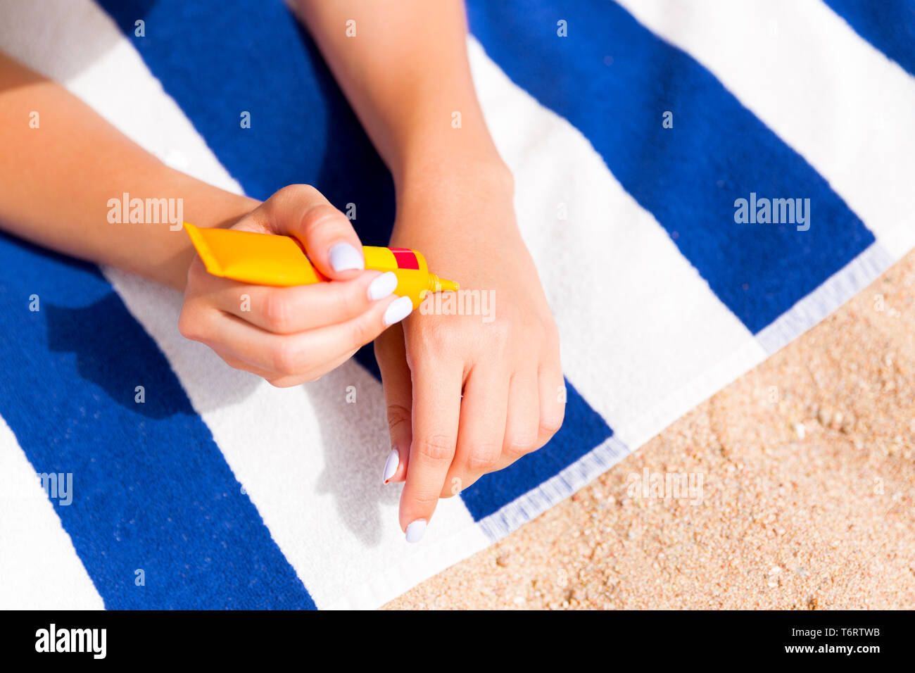 Woman hands putting sunscreen from a suncream bottle. - Stock Image