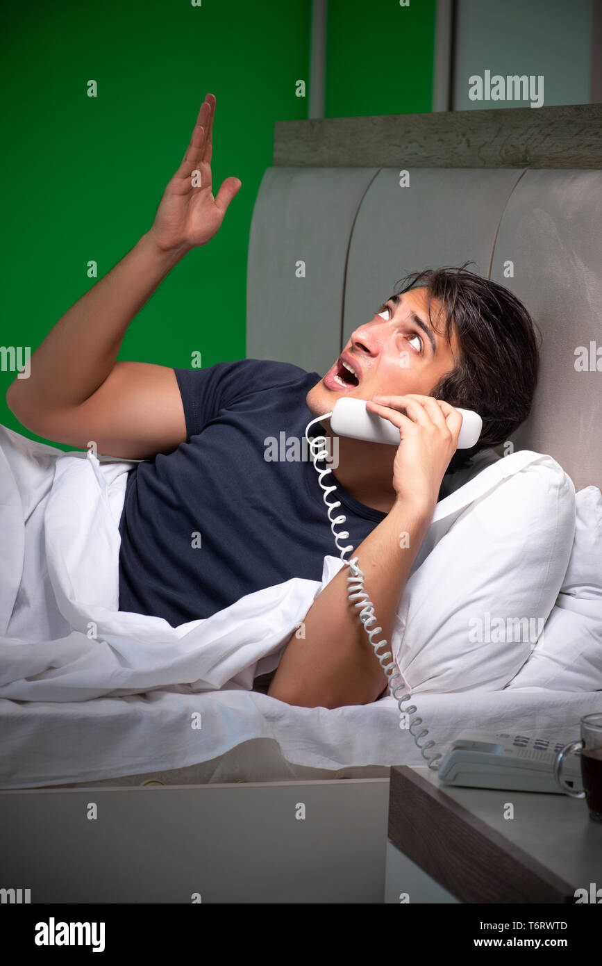 Young handsome man suffering from insomnia at home - Stock Image